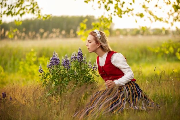 Lettische frau in traditioneller kleidung im feld Premium Fotos