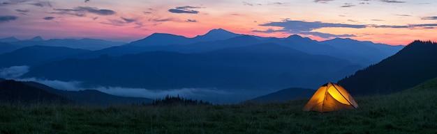 Leuchtendes orangefarbenes zelt in den bergen unter dramatischem abendhimmel Premium Fotos
