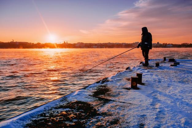 Leute am pier beobachten den sonnenuntergang Premium Fotos