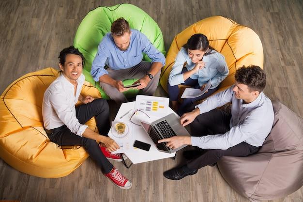 Leute arbeiten an beanbag stühle in trendy büro Kostenlose Fotos