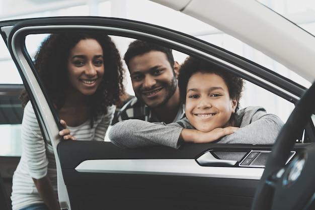 Leute, die durch autofenster-familien-kauf-auto schauen. Premium Fotos
