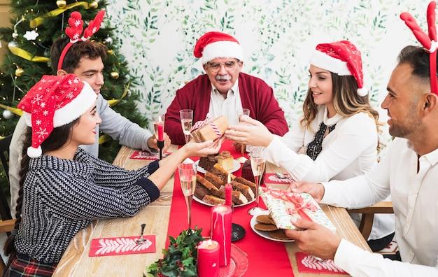 Leute, die einander am festlichen tisch geschenke geben Kostenlose Fotos