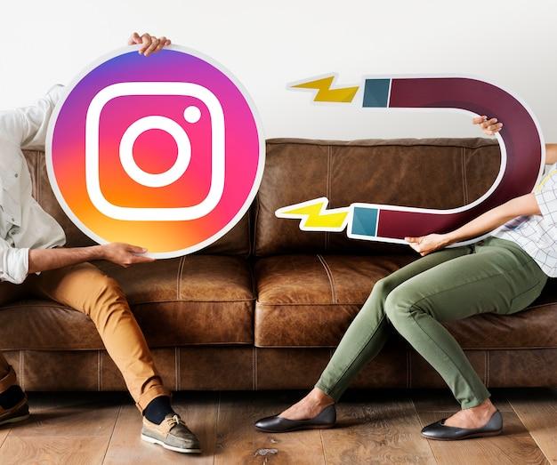 Leute, die eine instagram-ikone anhalten Kostenlose Fotos