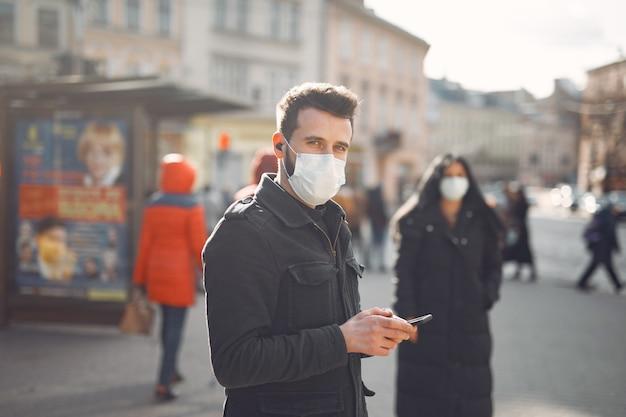 Leute, die eine schutzmaske tragen, die auf der straße steht Kostenlose Fotos