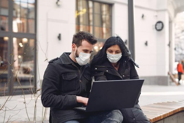 Leute, die eine schutzmaske tragen, die in einer stadt mit einem laptop sitzt Kostenlose Fotos