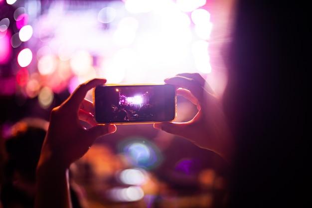 Leute, die fotos mit intelligentem telefon während des live-musikkonzerts und -menge machen Premium Fotos