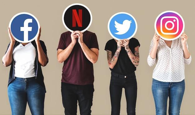 Leute, die ikonen von digitalen marken halten Kostenlose Fotos
