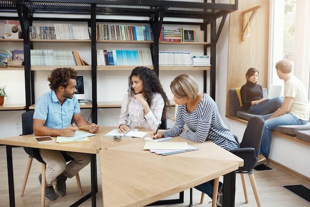 Leute, die im team arbeiten. drei junge geschäftspartner mit perspektive sitzen in der bibliothek und diskutieren über details und gewinne des startup-projekts. teamwork-konzept. Kostenlose Fotos