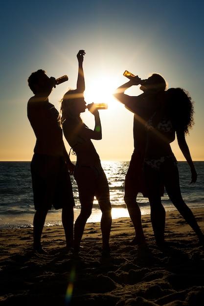Leute, die party am strand mit getränken haben Premium Fotos