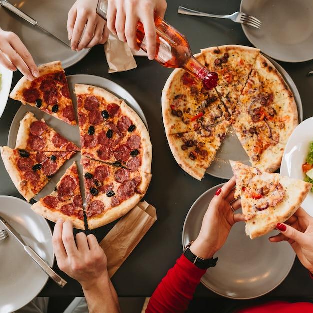Leute, die pizza in einem restaurant essen Premium Fotos