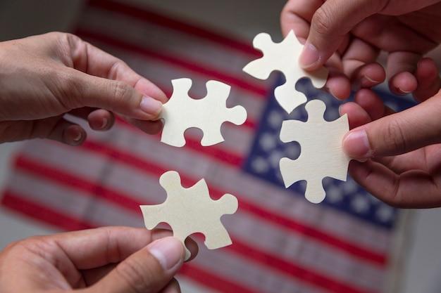 Leute, die puzzle zusammenbauen und teamunterstützung mit amerika-staatsflagge darstellen. Premium Fotos