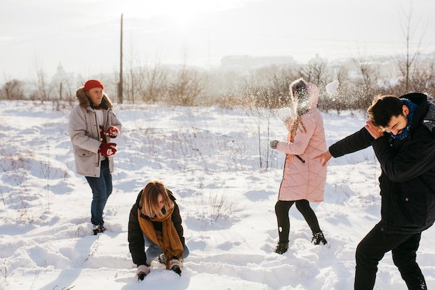 Leute, die schneebälle im winterwald spielen Kostenlose Fotos