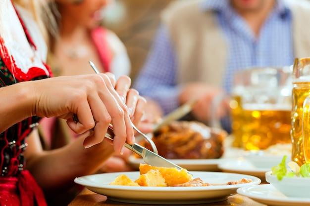 Leute, die schweinebraten im bayerischen restaurant essen Premium Fotos