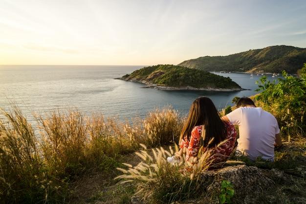 Leute, die sich lieben und ein paar sind, das zusammen auf einem hügel sitzt und einen blick auf die stadt hat Premium Fotos