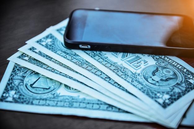 Leute, die smartphone verwenden, um online durch internet, smartphone und us-dollar auf hölzernem für das einkaufen oder die einsparung und die investition zu kaufen Premium Fotos