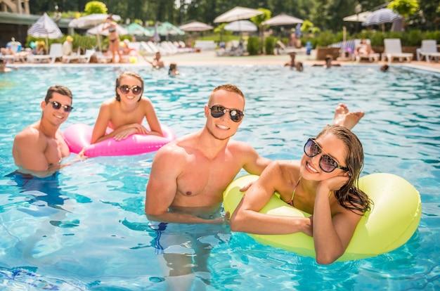 Leute, die spaß im swimmingpool, lächelnd haben. Premium Fotos