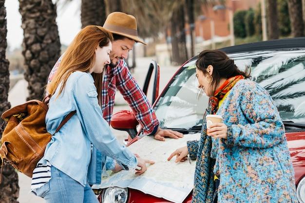 Leute, die straßenkarte nahe auto betrachten Kostenlose Fotos