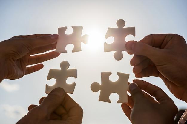 Leute, die vier puzzleteile zusammensetzen wollen. Premium Fotos