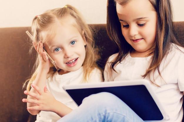 Leute-, familien-, technologie- und kinderkonzept - glückliche kleine mädchen, die zu hause mit tablet-pc-computer spielen Premium Fotos
