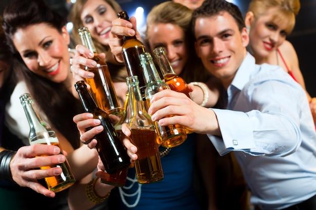 Leute im club oder in der bar, die bier trinken Premium Fotos