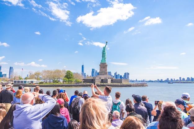 Leute machen foto vom freiheitsstatuen, new york city, ny, usa Premium Fotos