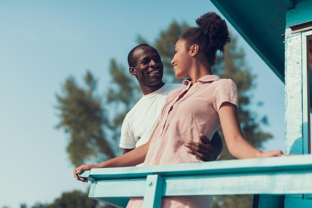 Leute stehen und schauen vom balkon des strandhauses Premium Fotos