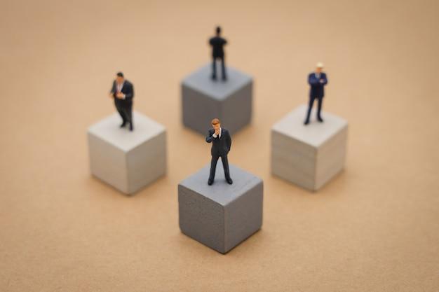 Leutegeschäftsleute der miniatur 4, die auf hölzernem würfel stehen investitionsanalyse Premium Fotos
