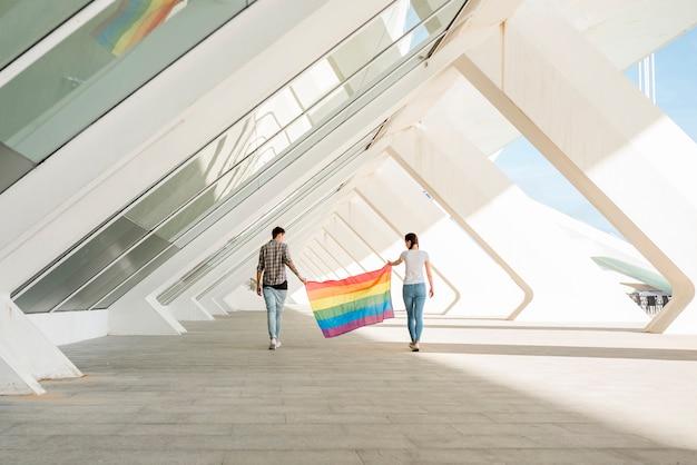 Lgbt-paare, die regenbogenflagge halten Kostenlose Fotos