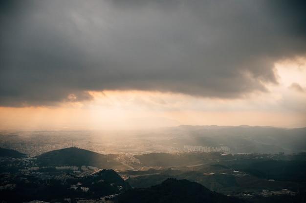 Lichtstrahl, der durch dunklen himmel über dem stadtbildberg eindringt Kostenlose Fotos