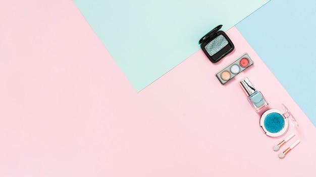 Lidschatten-palette; kompaktes pulver; nagellack flasche und pinsel auf pastell hintergrund Kostenlose Fotos