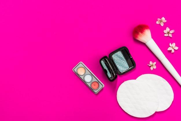 Lidschatten-palette; make-up pinsel; wattepads und blume auf rosa hintergrund Kostenlose Fotos