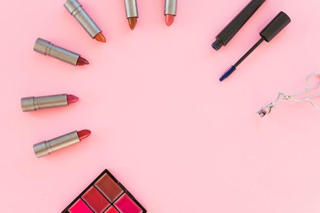 Lidschatten-palette; verschiedene lippenstift-töne; wimperntusche; über rosa hintergrund angeordnet Kostenlose Fotos