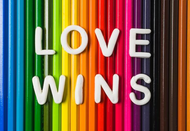 Liebe gewinnt wörter und lgbt-flagge von bleistiften Kostenlose Fotos