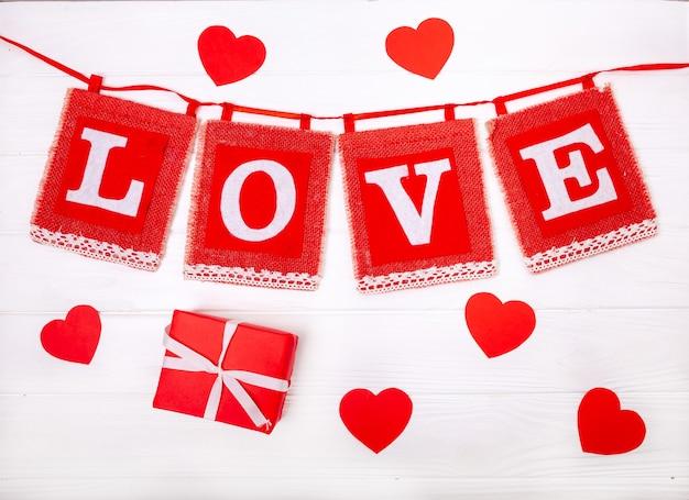 Liebe inschrift mit herzen und geschenken auf einem hölzernen weißen hintergrund Premium Fotos