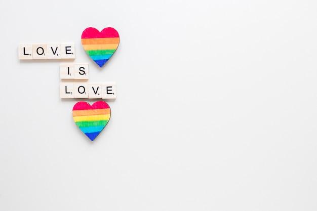 Liebe ist liebesaufschrift mit zwei regenbogenherzen Kostenlose Fotos