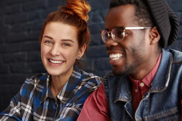 Liebe, jugend und freundschaft. hübsche frau mit ingwerhaar gekleidet im blauen karierten hemd, das mit niedlichem lächeln schaut Kostenlose Fotos