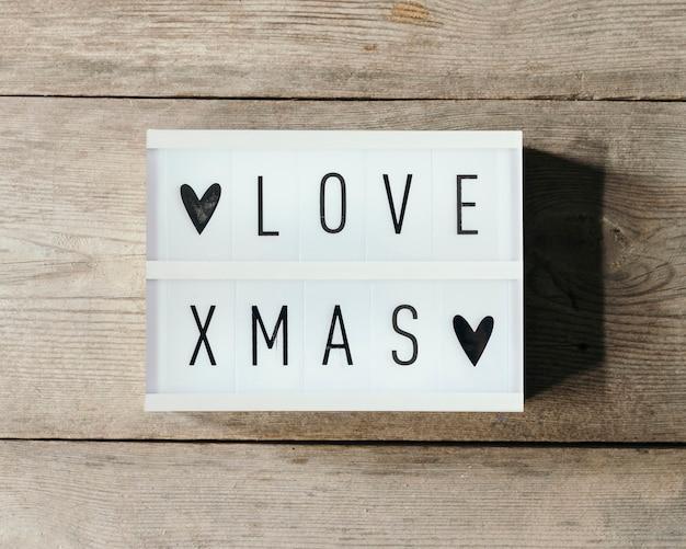 Liebe weihnachtstext in led-tafel mit holzhintergrund Kostenlose Fotos