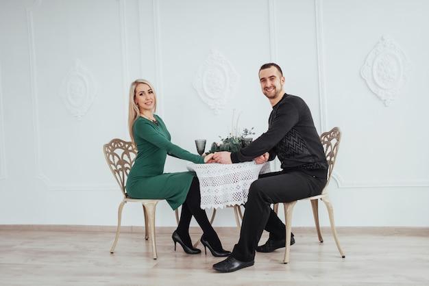 Lieben sie, am tischpaarmann und -frau mit weingläsern auf weiß im restaurant zu sitzen. valentinstag abendessen Premium Fotos