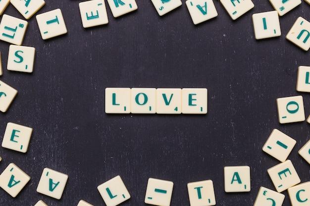 Lieben sie das wort, das auf dem schwarzen hintergrund vereinbart wird, der durch scrabblebuchstaben umgeben wird Kostenlose Fotos