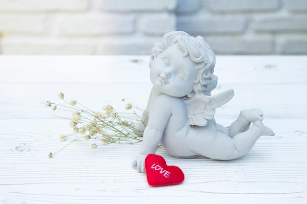 Lieben sie rotes herz des mitteilungs-valentinsgrußes mit amorstein auf weißem ziegelsteinhintergrund Premium Fotos