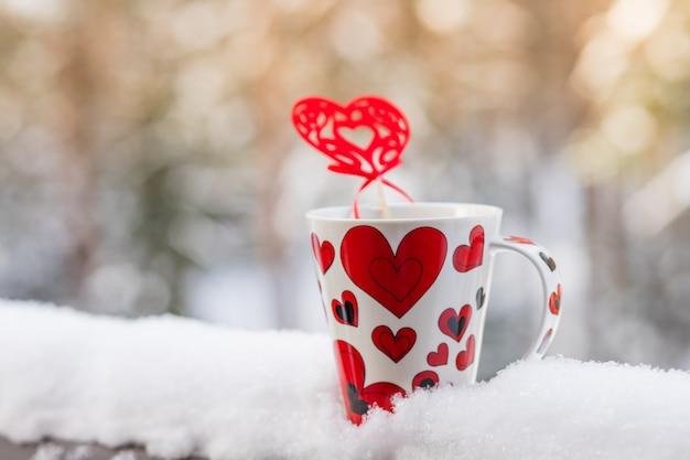 Lieben sie zur coffe zeit, zum weihnachtskonzept, zum becher und zur roten herzdekoration auf einem schneebalkon. Premium Fotos