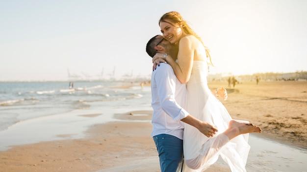 Liebenswerte glückliche junge paare, die am strand umfassen Kostenlose Fotos