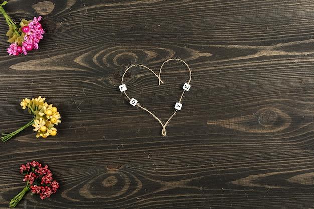 Liebesbrief mit blumen auf hölzernem hintergrund Premium Fotos