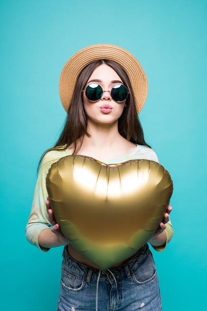 Liebesfrau lächelnd, die goldenen herzförmigen ballon hält. nette schöne junge frau in der liebe lokalisiert auf grün Kostenlose Fotos