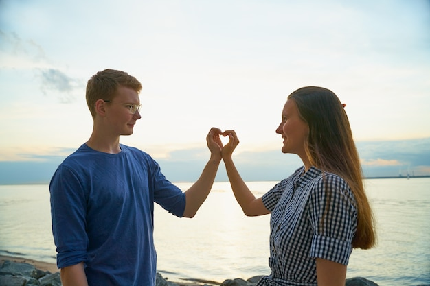 Liebesgeschichte von zwei, von jungen und von mädchen, die herz mit den fingern machen Premium Fotos