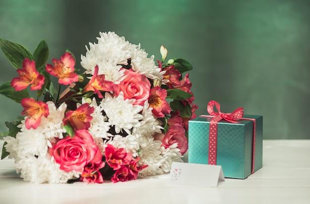 Liebeshintergrund mit rosa rosen, blumen, geschenk auf tisch Kostenlose Fotos