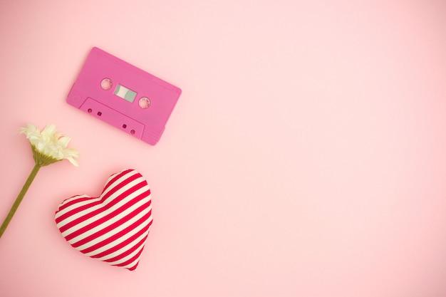 Liebesmusik. valentinstaghintergrund mit tonbandkassette, blume und einem roten herzen. Premium Fotos