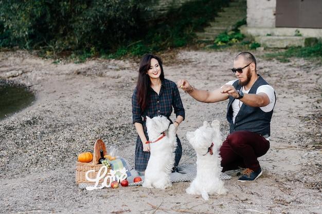 Liebespaar am strand spielen mit ihren weißen hunden Premium Fotos