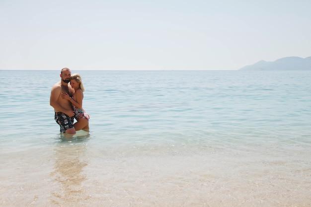 Liebespaar, das flitterwochen am strand in der lagune mit
