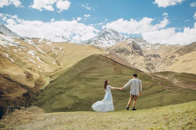 Liebespaar geht im hintergrund von hohen bergen mit gletschern an der spitze Kostenlose Fotos